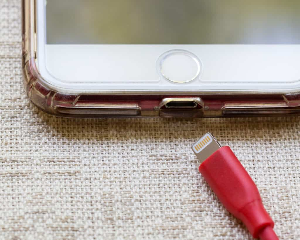 A white iPhone with a red charging colored cable.